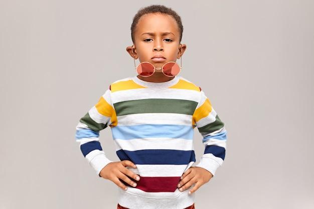 Horizontaler schuss des kühlen gutaussehenden afroamerikanischen kindes, das selbstbewussten gesichtsausdruck hat, der hände auf seiner taille hält, stilvolle runde rosatöne, die seine nase herunterfallen. kindheits- und modekonzept