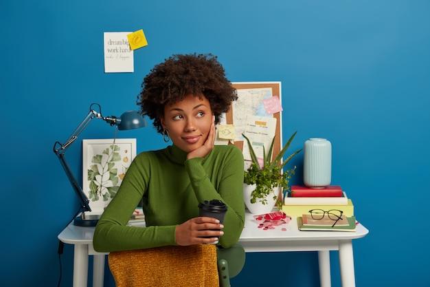 Horizontaler schuss des nachdenklichen afroamerikaners im grünen pullover, trinkt leckeren kaffee zum mitnehmen, posiert auf stuhl und schaut weg, hat pause nach dem studium, posiert gegen desktop im arbeitszimmer.