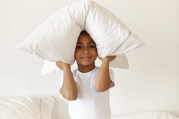 Horizontaler schuss des niedlichen freudigen afroamerikanischen kleinen jungen, der pyjamas trägt, die auf schlafzimmer sitzen