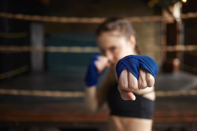 Horizontaler schuss des stilvollen jungen frauenboxers, der blaue handwickel trägt, die drinnen trainieren, sich für den boxkampf bereit machen und den arm ausstrecken