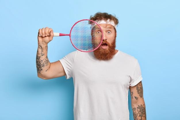 Horizontaler schuss des verängstigten rothaarigen tennisspielers hält schläger, während er gegen die blaue wand aufwirft