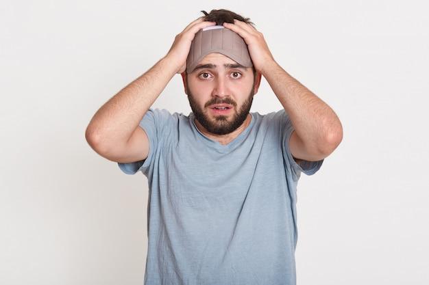 Horizontaler schuss des verwirrten hilflosen jungen mannes, der in panik ist, arme auf kopf hält und direkt die schlafmaske trägt