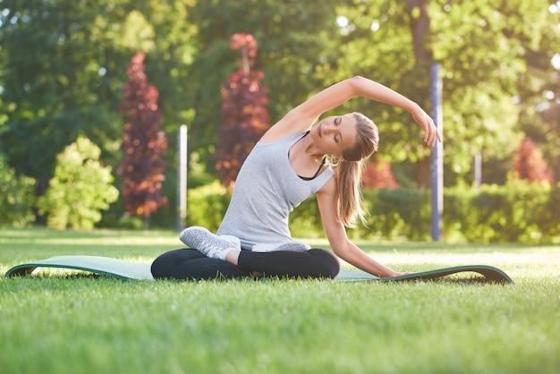 Horizontaler schuss einer jungen schönen frau, die yoga am park sitzt, der auf übungsmatte sitzt, die ihr rückenflexibilitäts-energieharmoniegesundes lebensstilkonzept streckt.