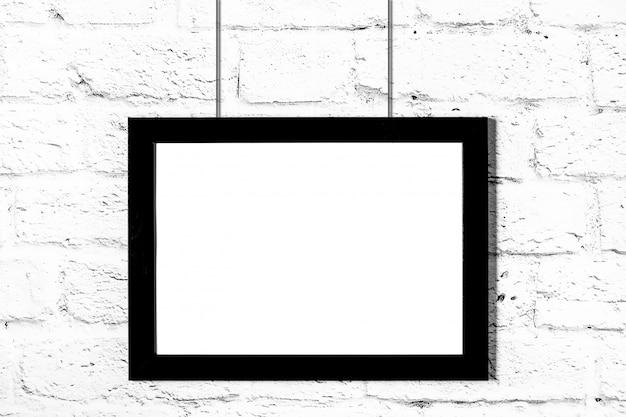 Horizontaler schwarzer fotorahmen, der an der backsteinmauer hängt. modell mit textfreiraum
