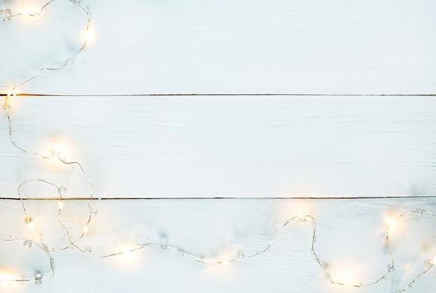 Horizontaler texturhintergrund des weißen holzes mit gelber girlande und kopierraum.