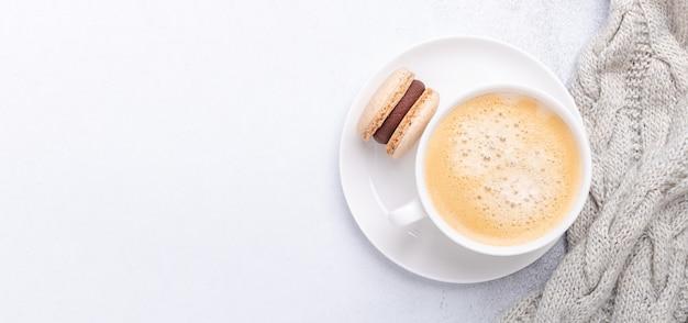 Horizontales banner mit strickschal, kaffee und schokoladenmacaron auf steinhintergrund. gemütliche herbstkomposition. flache lage, ansicht von oben - image