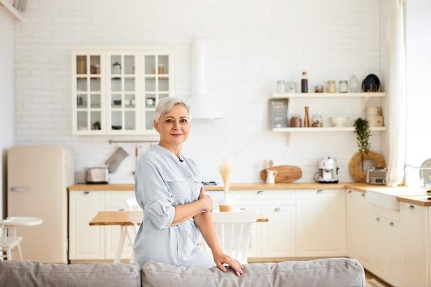 Horizontales bild der herrlichen freudigen älteren sechzigjährigen hausfrau, die ruhe hat, nachdem sie alle räume gereinigt hat, fröhlichen gesichtsausdruck hat und im wohnzimmer mit küche in steht