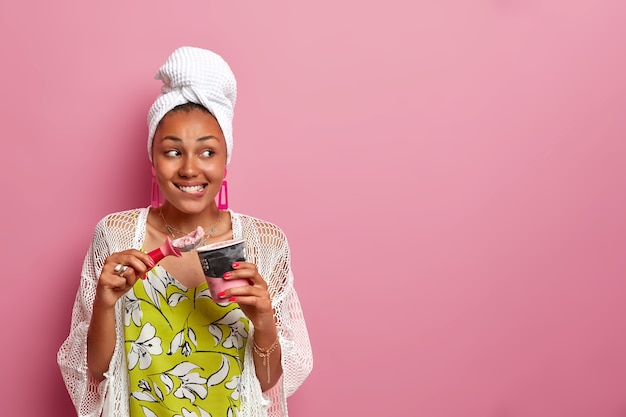 Horizontales bild der lächelnden dunkelhäutigen dame trägt handtuch auf kopf, lässiges outfit, befriedigt naschkatzen mit köstlichem kaltem eis, hält löffel, tasse gefrorenes dessert, isoliert auf rosa wand
