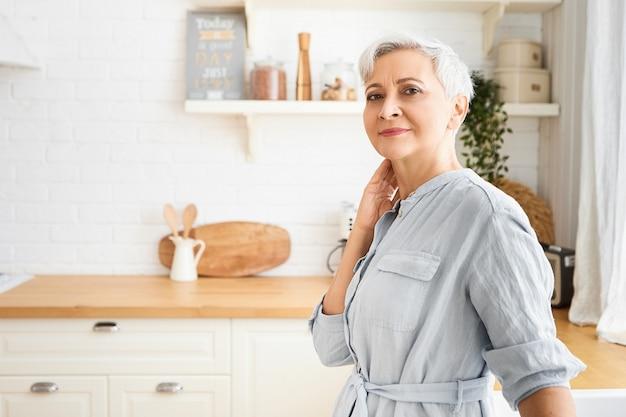 Horizontales bild der reifen schönen älteren frau, die stilvolles blaues kleid trägt, das innen mit sauberer gemütlicher küchentheke und utensilien aufwirft, mit glücklichem lächeln schauend