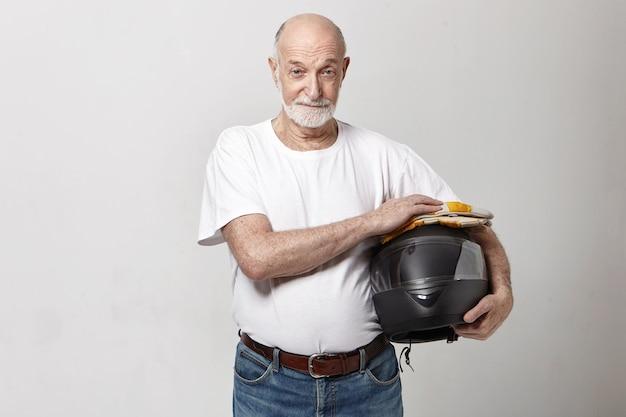 Horizontales bild des älteren kaukasischen mannes mit dem dicken grauen bart, der im studio aufwirft