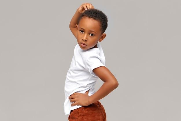 Horizontales bild des hübschen lustigen achtjährigen dunkelhäutigen kleinen jungen, der isoliert vorgibt, modemodell zu sein,