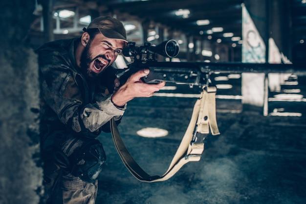 Horizontales bild des soldaten sitzt aus den grund auf einem knie nahe spalte und schreit. er zielt. guy benutzt dafür ein gewehr. er schaut durch die linse des gewehrs.