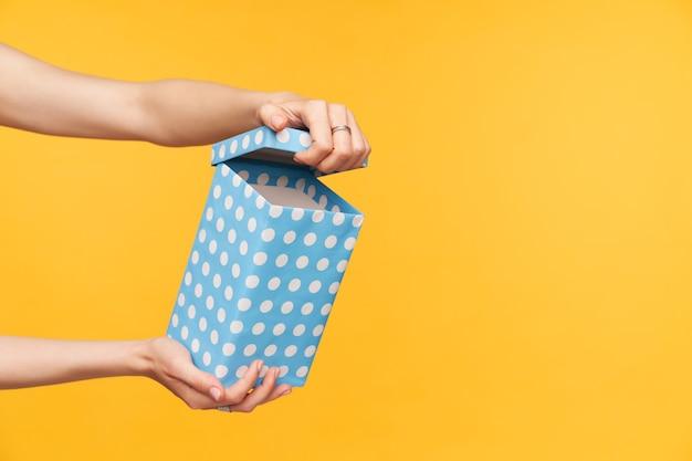 Horizontales foto der hand der hübschen dame mit der nackten maniküre, die überraschung geetet und geschenk-minze-punktbox auspackt, während über gelbem hintergrund stehend