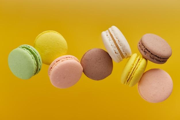 Horizontales foto der makrone. bunter kuchen macaron mit pastelltönen in chaotischer levitation auf einer gelben oberfläche. draufsicht auf mandelkekse.