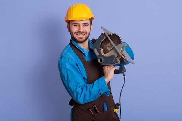 Horizontales foto des gut aussehenden gutaussehenden glücklichen arbeiters, der werkzeug in beiden händen hält, direkt in die kamera schaut, aufrichtig lächelt, braune schürze, blauen overall und gelben helm tragend. arbeitskonzept.