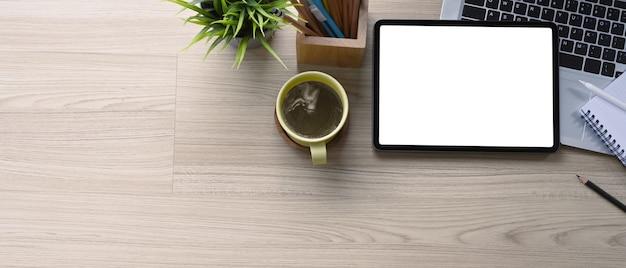 Horizontales foto des modernen arbeitsplatzes mit digitalem tablet, laptop, pflanze, kaffeetasse und kopienraum auf holzschreibtisch.