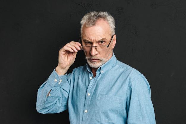 Horizontales foto des reifen unrasierten mannes 60s mit grauem haar, das brillen mit starkem blick und berührenden brillen trägt, lokalisiert über schwarzer wand