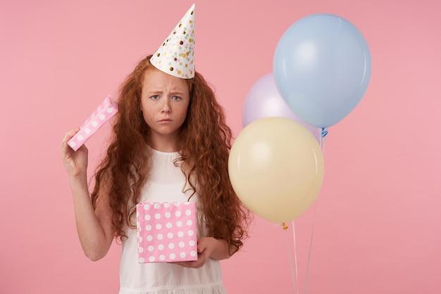 Horizontales foto des verärgerten lockigen mädchens mit dem roten langen haar, das weißes kleid und geburtstagskappe feiert, feiert feiertag, schaut in der kamera traurig mit geschenkbox in den händen, posierend über rosa studiohintergrund