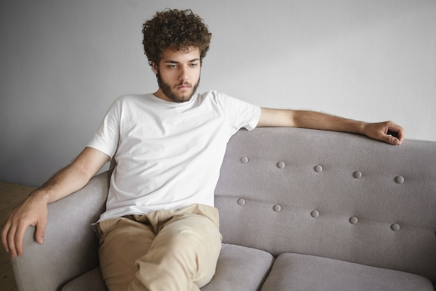 Horizontales isoliertes porträt des attraktiven jungen kaukasischen mannes mit voluminösem haar und dickem bart, der beiläufig auf grauem sofa zu hause sitzt und vor ihm schaut und nachdenklichen nachdenklichen ausdruck hat