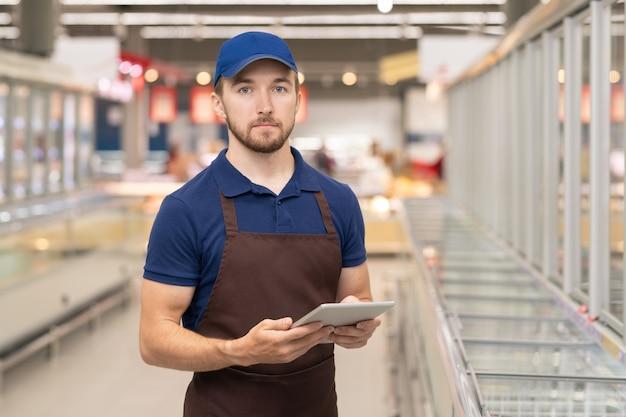 Horizontales mittleres porträt eines modernen jungen mannes in uniform, der mit verschränkten armen im laden arbeitet