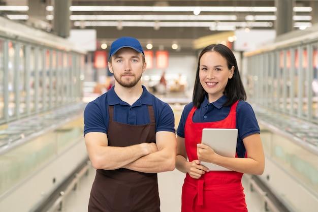 Horizontales mittleres porträt, wenn mann und frau in uniform im supermarktgang zusammenstehen