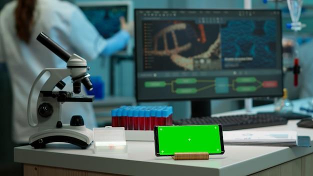 Horizontales mobiltelefon mit grünem bildschirm, das im labor mit mock-up-vorlage arbeitet, chroma-key-anzeige, während ein professioneller ingenieur die virusentwicklung im hintergrund testet. hightech-entwicklungslabor.