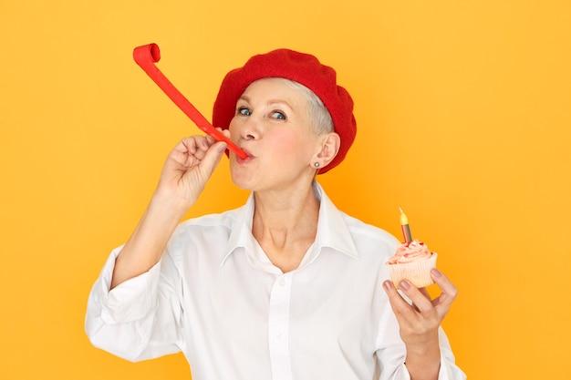 Horizontales porträt der aufgeregten kurzhaarigen blonden frau mittleren alters in der eleganten roten baskenmütze, die geburtstagskuchen mit kerze hält, die partypfeife bläst.