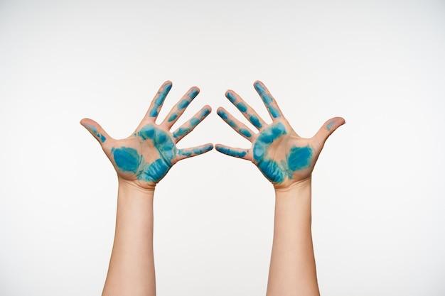 Horizontales porträt der erhabenen weiblichen arme, die mit blauer farbe gemalt werden und alle finger getrennt halten, während sie auf weiß posieren. körpersprachenkonzept