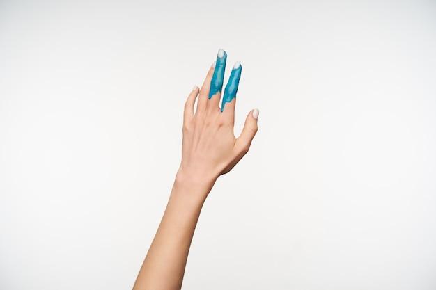 Horizontales porträt der hand der hübschen jungen dame, die in der blauen farbe gemalt wird, während sie es nach oben hebt und auf weiß aufwirft. körpersprachenkonzept