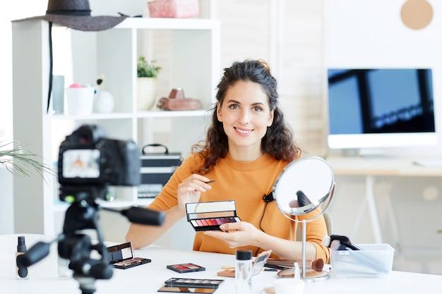 Horizontales porträt der jungen frau, die lippenstiftaufzeichnungsvideo für ihren schönheitsblogkanal hält