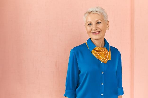 Horizontales porträt der modischen selbstbewussten reifen kaukasischen frau mit blonder pixie-frisur, die auf leere rosa wand aufwirft