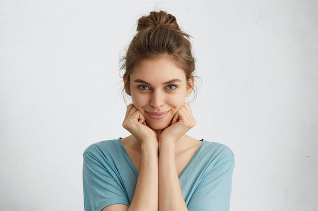 Horizontales porträt der niedlichen jungen frau mit blauen augen und sanftem lächeln, das hände unter dem kinn hält, das zufrieden und sorglos schaut.