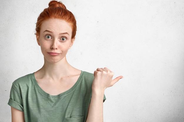 Horizontales porträt der verwirrten ingwerfrau mit haarknoten, gekleidet in lässigem t-shirt und ahnungslosem blick, zeigt an leerem kopienraum an