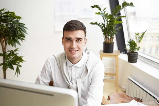 Horizontales porträt des attraktiven jungen brünetten männlichen architekten, der an seinem arbeitsplatz vor dem computer sitzt, während er an neuem wohnprojekt unter verwendung der 3d-cad-anwendung arbeitet, glücklichen ausdruck habend