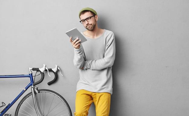 Horizontales porträt des bärtigen kerls, der in tablette mit ernstem ausdruck beim lesen etwas schaut. selbstbewusster männlicher student, der sich auf den unterricht vorbereitet und ein radrennen veranstaltet