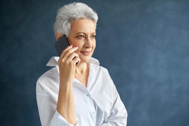 Horizontales porträt des beschäftigten kaukasischen weiblichen managers mittleren alters im weißen hemd, das handy hält