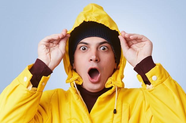 Horizontales porträt des betäubten betäubten mannes trägt gelben regenmantel, kapuze und hut, schaut aus dem fenster, sieht starken regen draußen, sollte das gehen im park mit freund verschieben. menschen und mimik