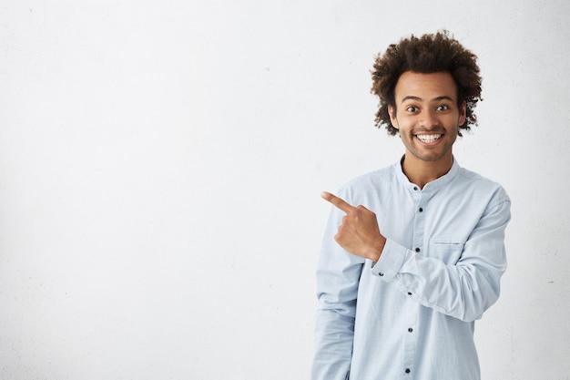 Horizontales porträt des dunkelhäutigen gutaussehenden mannes, der ein breites lächeln trägt, das formelles weißes hemd trägt