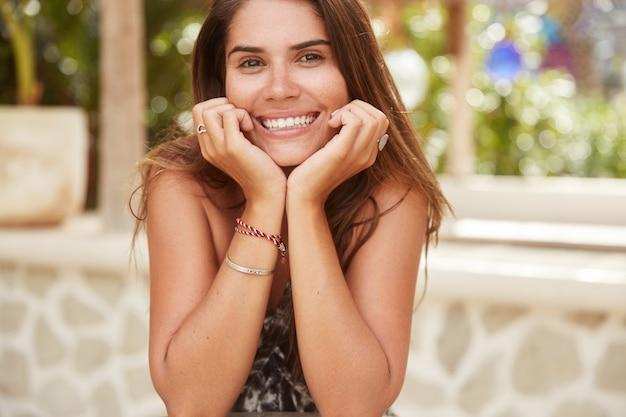 Horizontales porträt des entzückten fröhlichen weiblichen modells mit breitem lächeln hält hände unter kinn, rekonstruieren im café, hat sommerruhe auf tropischer insel