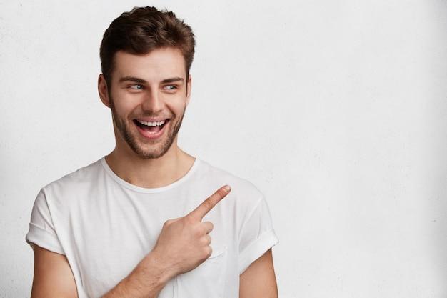Horizontales porträt des fröhlichen unrasierten blauäugigen mannes im lässigen weißen t-shirt, zeigt mit dem vorderfinger am leeren kopierraum an, wirbt für etwas, hat positiven ausdruck. menschen, werbekonzept