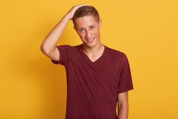 Horizontales porträt des gutaussehenden männlichen erwachsenen, der hand auf seinem kopf hält, informationen analysiert oder entscheidung trifft