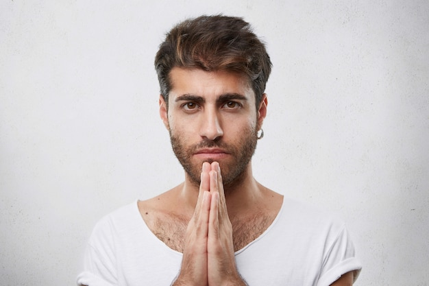 Horizontales porträt des gutaussehenden mannes mit der trendigen frisur und dem bart, die ohrring und weißes t-shirt tragen, die seine hände zusammenhalten und beten, augen voller glauben zu haben, um besser nach etwas zu fragen