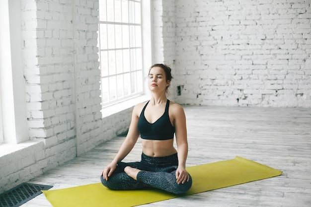 Horizontales porträt des herrlichen europäischen mädchens mit dem haarknoten, der auf grüner matte in lotushaltung sitzt und meditiert. junge dunkelhaarige frau, die am frühen morgen vor der arbeit yoga-meditation macht