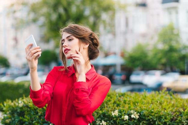 Horizontales porträt des hübschen mädchens, das im park steht. sie trägt eine rote bluse und eine schöne frisur. sie schaut zum telefon in der hand und träumt.