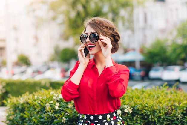 Horizontales porträt des hübschen mädchens in der sonnenbrille, die im park geht. sie trägt eine rote bluse und eine schöne frisur. sie spricht am telefon.