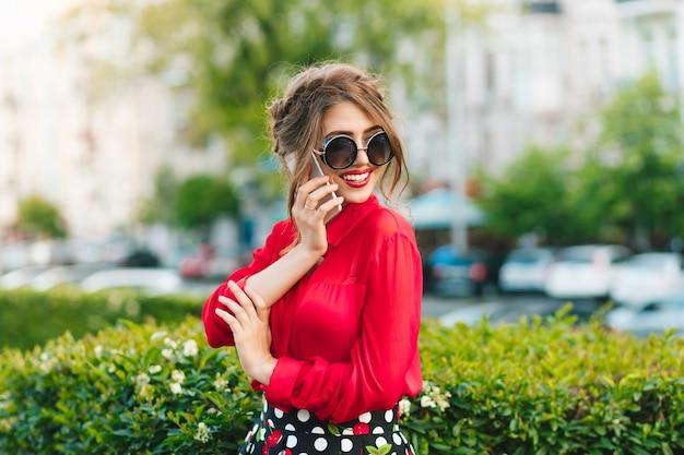 Horizontales porträt des hübschen mädchens in der sonnenbrille, die im park steht. sie trägt eine rote bluse und eine schöne frisur. sie spricht am telefon.