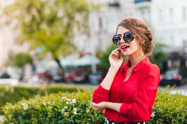 Horizontales porträt des hübschen mädchens in der sonnenbrille, die zur kamera im park aufwirft. sie trägt eine rote bluse und eine schöne frisur. sie schaut weit weg.