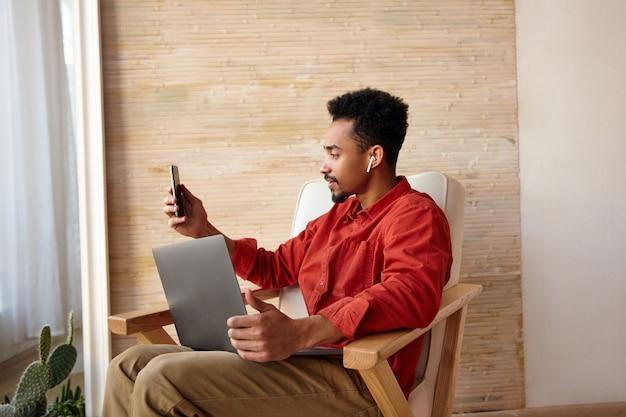Horizontales porträt des jungen bärtigen dunkelhäutigen kerls mit dem kurzen haarschnitt, der im stuhl vor dem fenster sitzt und videoanruf mit seinem smartprone hat, lokalisiert auf hauptinnenraum