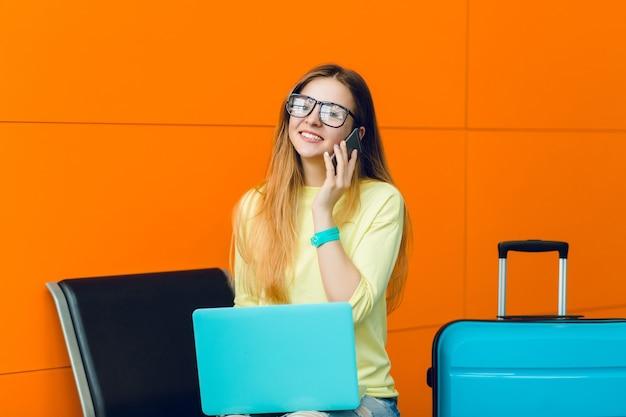Horizontales porträt des jungen mädchens im gelben pullover, der auf stuhl auf orange hintergrund sitzt. sie hat lange haare und eine schwarze brille. sie telefoniert und lächelt in die kamera.