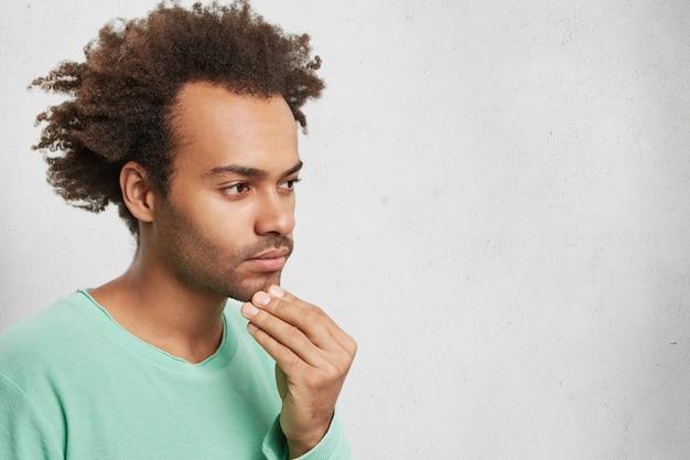 Horizontales porträt des nachdenklichen mischlingsmannes mit afro-frisur, hält hand am kinn